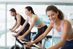 Fit people in a spin class with woman smiling at camera Royalty Free Stock Image