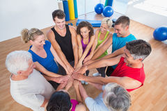 Fit people stacking hands at health club Royalty Free Stock Image