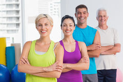 Fit people standing arms crossed at gym. Portrait of confident fit people standing arms crossed at gym Royalty Free Stock Images