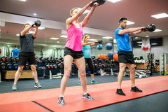 Fit people swinging kettlebell weights Royalty Free Stock Image