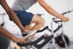 Fit people working out on the exercise bikes Stock Images