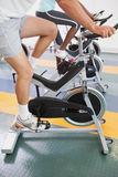 Fit people working out on the exercise bikes Stock Photos