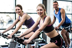 Fit people working out at spinning class Stock Photos