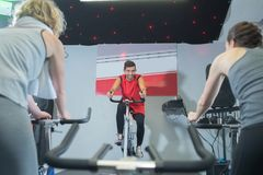 Fit people working out at spinning class stock images