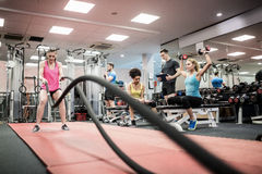 Fit people working out in weights room Royalty Free Stock Images