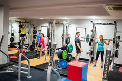 Fit people working out in weights room Royalty Free Stock Image