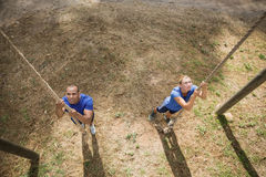 Fit person climbing down the rope during obstacle course. In boot camp royalty free stock photo