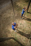 Fit person climbing down the rope during obstacle course. In boot camp stock photo