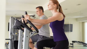 Fit positive couple working out on exercise bikes at gym. Woman using smartwatch checking vitals stock video