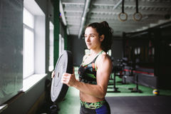 Fit power athletic confident young woman crossfit trainer doing exercises with heavy weight barbell plate in gym rising hand. Fitn Stock Images