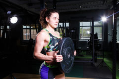 Fit power athletic confident young woman crossfit trainer doing exercises with heavy weight barbell plate in gym rising hand. Fitn Royalty Free Stock Photos