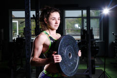 Fit power athletic confident young woman crossfit trainer doing exercises with heavy weight barbell plate in gym rising hand. Fitn Stock Photos