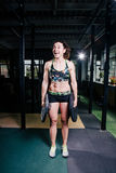 Fit power athletic confident young woman crossfit trainer doing exercises with heavy weight barbell plate in gym rising hand. Fitn Royalty Free Stock Photography