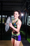 Fit power athletic confident young woman crossfit trainer doing exercises with heavy weight barbell plate in gym rising hand. Fitn Stock Photography
