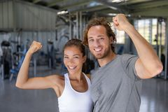Fit power couple happy flexing strong arms showing off success training at fitness gym - Smiling Asian woman. Caucasian man stock image