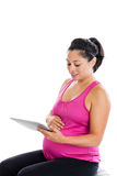 Fit pregnant woman looking at tablet PC Stock Photos