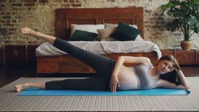 Fit pregnant woman is raising her leg lying on yoga mat on bedroom floor doing sports exercises. Healthy lifestyle stock video footage