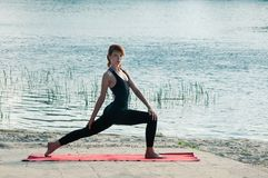 Fit pretty female practice yoga exercise outdoors stock photography