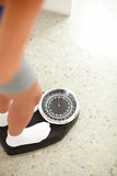 Fit pretty girl weighing herself in a scale Royalty Free Stock Images