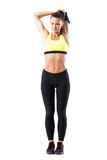 Fit pretty woman in sportswear stretching triceps muscles with hand behind neck. Full body length portrait isolated on white studio background Stock Photography