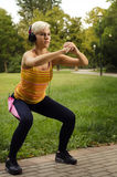 Fit pretty young woman doing squats in park royalty free stock images