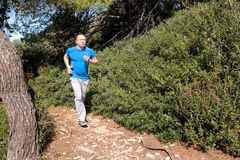 Fit runner man jogging for fitness running at running trail in beautiful landscape nature outdoors. Royalty Free Stock Photo