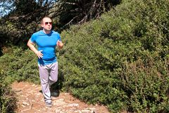 Fit runner man jogging for fitness running at running trail in beautiful landscape nature outdoors. Stock Photo