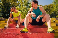 Fit runners resting on stairs after jogging. Healthy couple with headphones rest after running royalty free stock photo