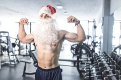 Fit santa shwoing his muscles in gym after christmas fitness tra. Ining Stock Photo