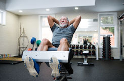 Fit senior man in gym working his abs, doing crunches. Royalty Free Stock Photo