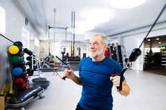 Fit senior man in gym working out with weights. Royalty Free Stock Photo