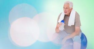Fit senior man holding water bottle on ball by bokeh Stock Image