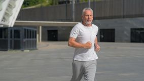 Fit senior man running in the city
