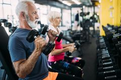 Fit senior sporty couple working out together at gym royalty free stock photo