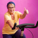 Fit senior woman doing thumbs up on bicycle. Stock Photos