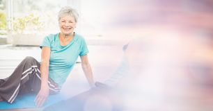 Fit senior woman exercising in yoga class stock photo