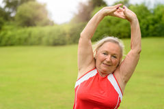 Fit senior woman performing yoga exercises. Fit athletic senior woman performing prayer pose yoga exercises at outdoor park with green grass and copy space Stock Photos