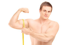 Fit shirtless guy measuring his muscle. Isolated on white background Stock Photography