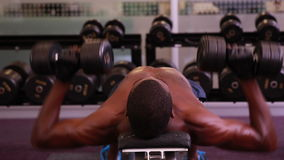 Fit shirtless man lifting dumbbells lying on bench stock video footage