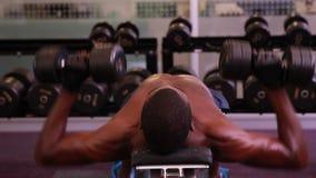 Fit shirtless man lifting dumbbells lying on bench Stock Photos