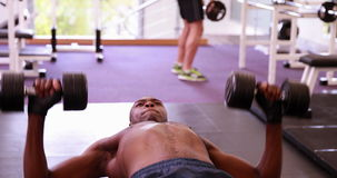 Fit shirtless man lifting dumbbells lying on bench. At the gym stock video footage