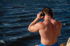 Fit slender athlete relax with earphones on shore Royalty Free Stock Photos