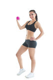 Fit slender woman training her arm using a pink dumbbell Royalty Free Stock Photos