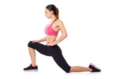 Fit slender woman working out. Attractive young fit slender woman working out doing exercises kneeling on the floor stretching her legs muscles, studio portrait Royalty Free Stock Photo