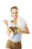 Fit and slim woman with towel over her shoulder eating a fresh salad Stock Photography