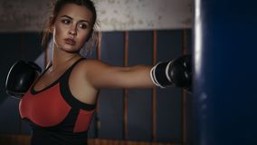 Fit slim young beautiful brunette woman boxing in sportswear. Da. Rk dim light. Toned image stock photography