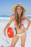 Fit smiling blonde in white bikini and straw hat holding beach ball Royalty Free Stock Photography