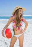 Fit smiling blonde in white bikini and straw hat holding beach ball Stock Photography