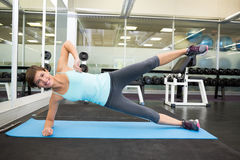 Fit smiling brunette doing pilates on exercise mat Royalty Free Stock Image
