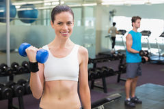 Fit smiling brunette lifting heavy black dumbbell Royalty Free Stock Photos